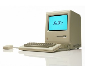 The first Macintosh computer, the 128k, on a white reflective surface.